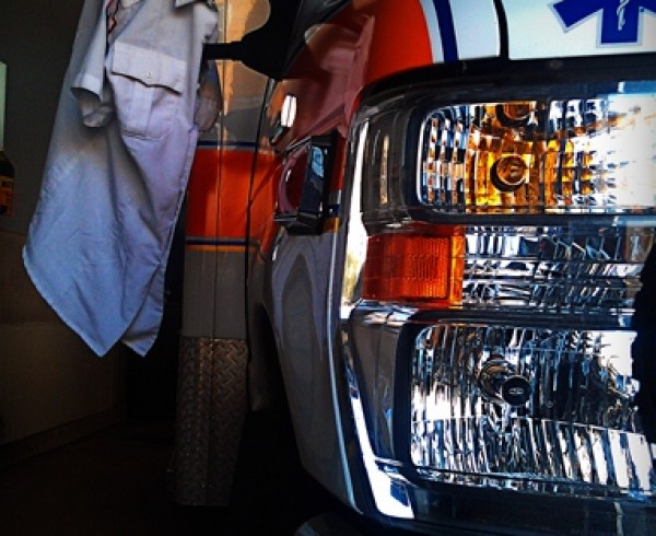 close up of ambulance with paramedic uniform hanging off side mirror