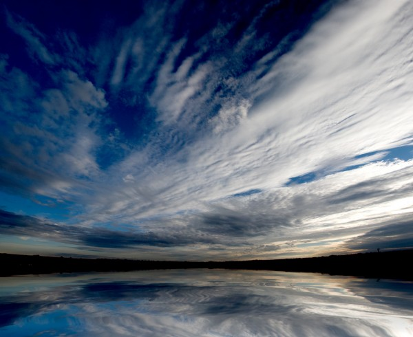 Fish-eye lens picture of rippling clouds in a deep blue sky reflected in still water